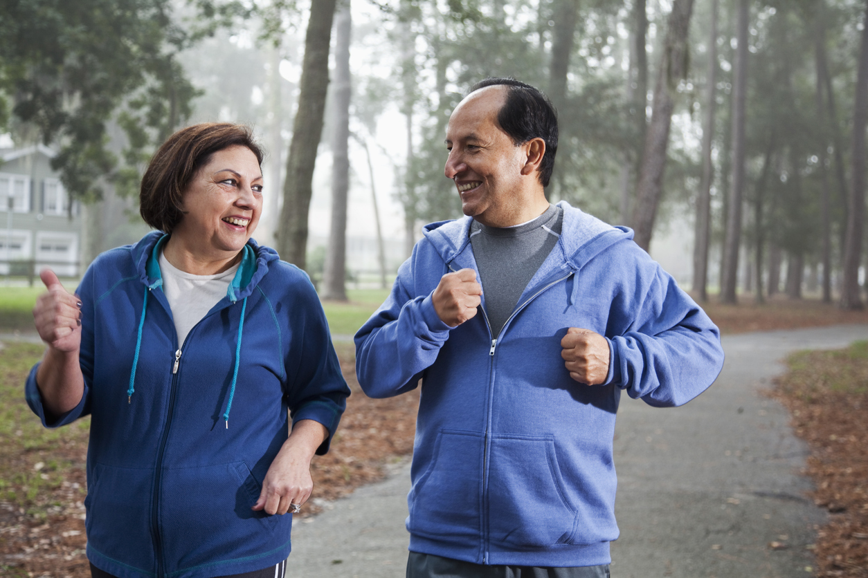 Senior Hispanic couple jogging in park